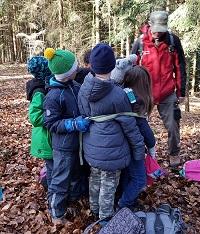 Kinder stellen den Baumumfang dar.